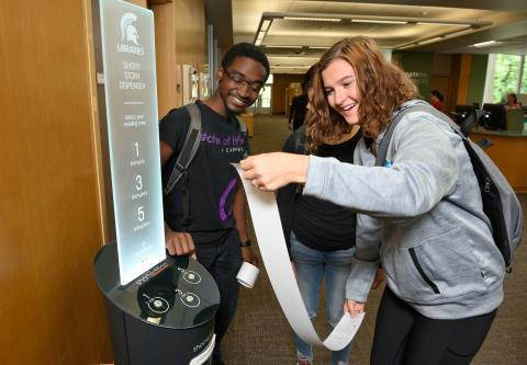 Three students enjoy the MSU Library's new Short Edition Kiosk